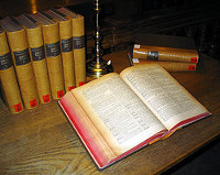 A Latin Dictionary open on a desk with reference books arranged behind it.