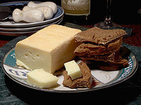 A brick and slices of Limburger cheese on a plate with bread.
