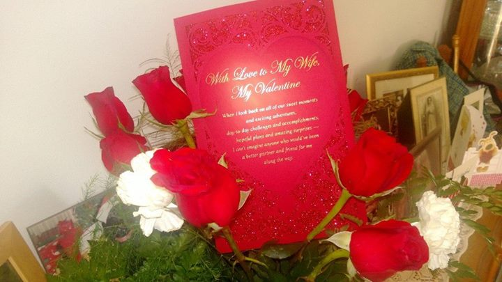 Roses and A Valentine Card Displayed with Family Pictures.