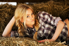 Image of a pretty blond girl in  flannel shirt on a hay bale.