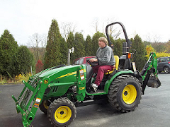 Image of Glory's Husband Tom on his John Deere Tractor.
