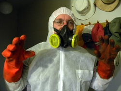 Picture of Raymond in protective clothing including respirator, coveralls, rubber gloves and cap.