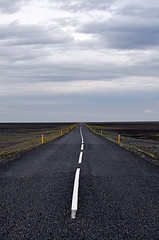 Picture of a straight road with white center markers.